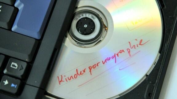 Eine DVD mit der Aufschrift 'Kinderpornographie' liegt im Laufwerk eines Notebooks