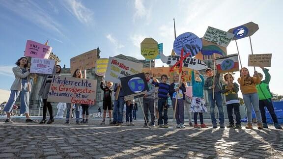 Kinder halten anlässlich des Weltkindertags vor dem Reichstag Transparente mit ihren Forderungen in die Höhe