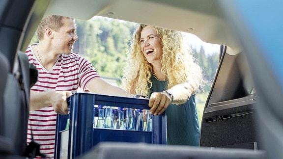 Ein Paar stellt ein Kasten Wasser in den Kofferraum eines Autos.
