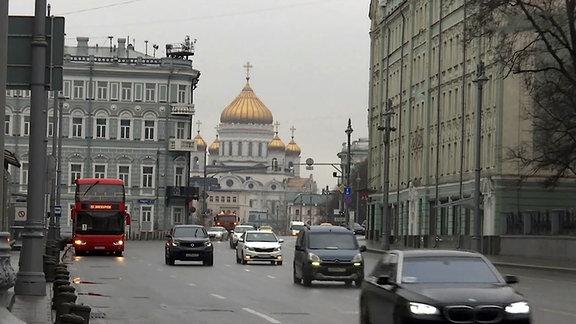 Autos auf einer Strasse, im Hintergrund eine Kirche