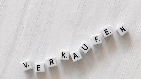 """Das Wort """"verkaufen"""" aus weißen Buchstabenwürfeln gelegt"""