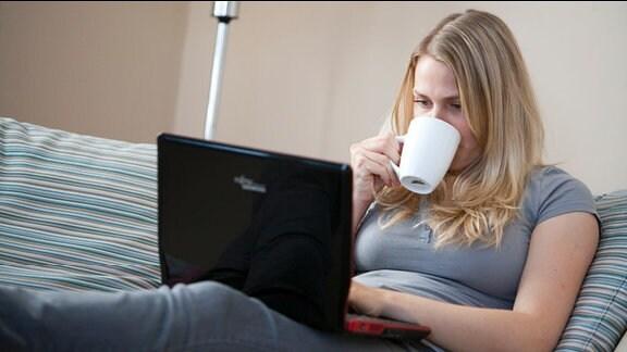 Eine kaffeetrinkende Frau schaut auf einen Laptop