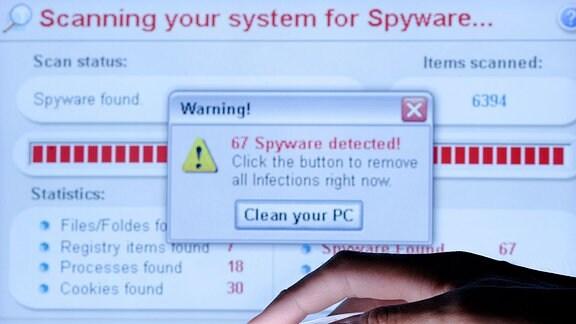 Eine Hand auf einer Maus vor einem Computermonitor, auf dem eine Virenwarnung angezeigt wird