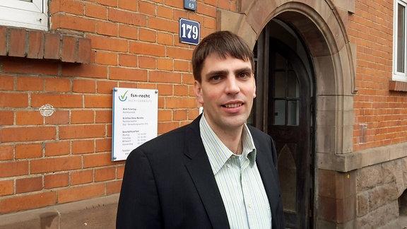 Rechtsanwalt Dirk Feiertag steht vor der Tür seiner Anwaltskanzlei in Leipzig