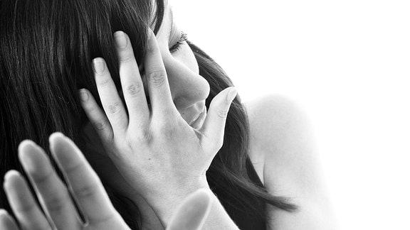 Frau verbirgt ihr Gesicht hinter einer Hand, die andere Hand hält sie abwehrend vor sich