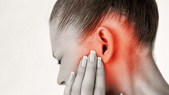 Eine junge Frau hält ihre Hand an ihr Ohr.