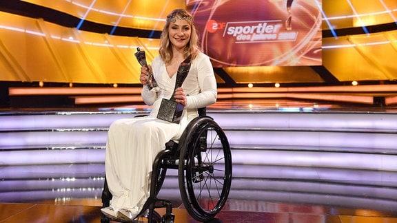 """Kristina Vogel im Rollstuhl und in langem weißen Kleid und mit glätzendem Haareif bei der bei der Gala """"SportlerIn des Jahres"""" 2018"""