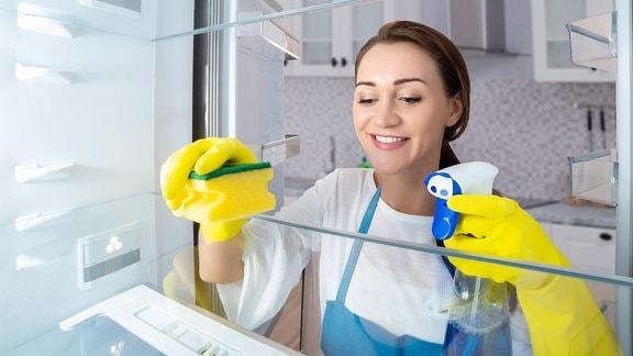 Eine Frau reinigt einen Kühlschrank