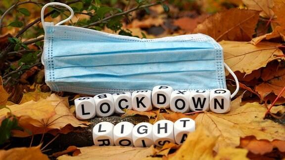 Ein blauer Mundschutz liegt auf Herbstlaub, davor bilden Würfel das Wort: Lockdown Light