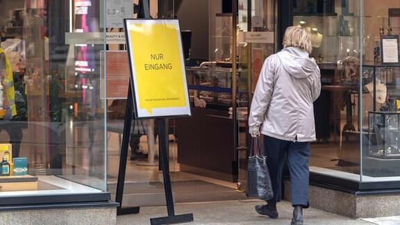 Eine Frau betritt ein Geschäft durch eine Tür, neben dem ein Schild mit der Aufschrift Nur Eingang steht