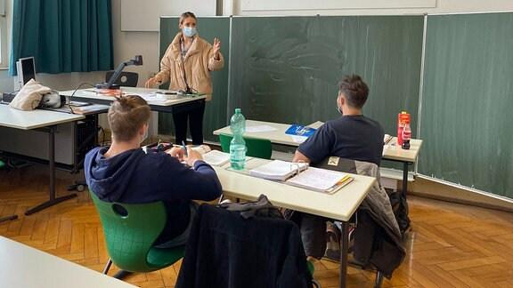 Lehrerin mit dicker Winterjacke und Mundschutzmaske