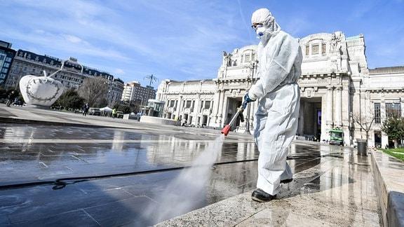 Ein Arbeiter im Schutzanzug desinfiziert die Piazza Duca d'Aosta vor dem Bahnhof Milano Centrale.