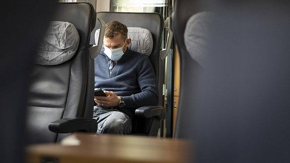 Ein Mann mit Mund-Nasen-Schutz sitzt in einem Zug