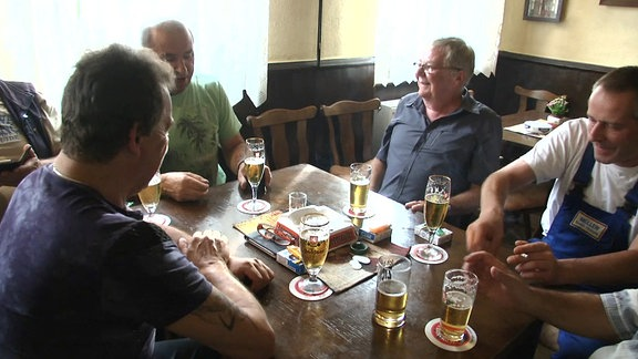 Männer sitzen an einem Stammtisch und unterhalten sich.