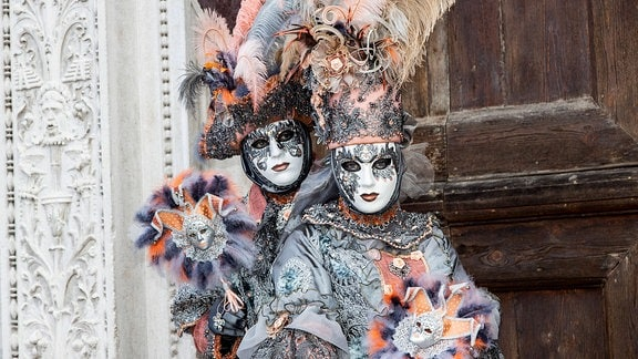 Zwei Personen mit bunten Kostümen und Masken.