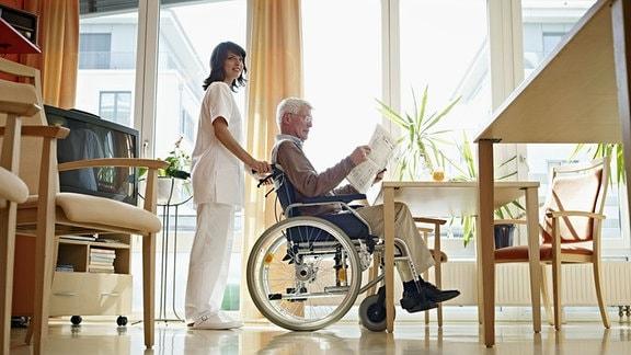 Altempflege - Pflegerin betreut Senior im Rollstuhl