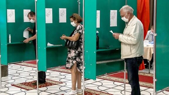 Menschen beim Wählen in den Wahlkabinen.