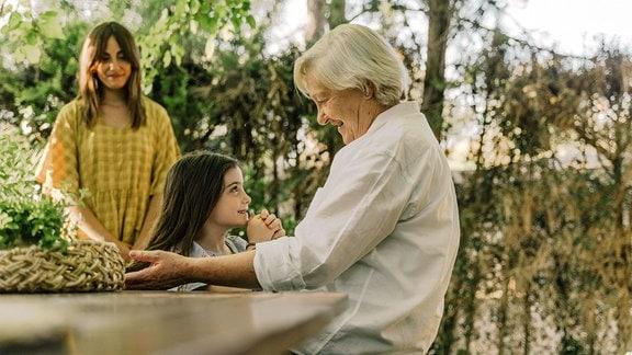 Oma und Enkelin, im Hintergrund steht die Mutter und schaut zu.