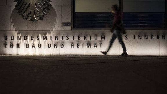 Eine Person laeuft entlang des Schriftzuges Bundesministerium des Innern