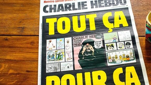 Charlie Hebdo Magazin liegt neben einer gefüllten Kaffeetasse auf einem Holztisch