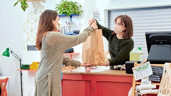 Frau mit Schutzmaske reicht Papier-Einkaufstasche an Kundin über die Theke an.