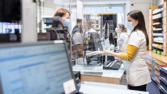 Eine Mitarbeiterin der Apotheke Stadelhofen übergibt einen Beutel mit fünf Antigen-Schnelltests.