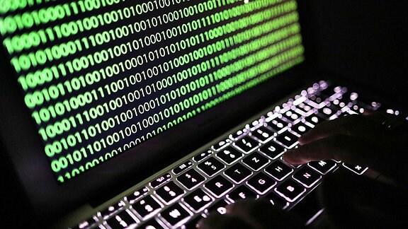 Auf dem Bildschirm eines Laptops ist der Binärcode zu sehen.