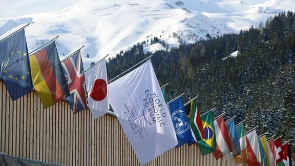 Fahnen verschiedener Staaten hängen an einem Gebäude in Davos, im Hintergrund schneebedeckte Berge.