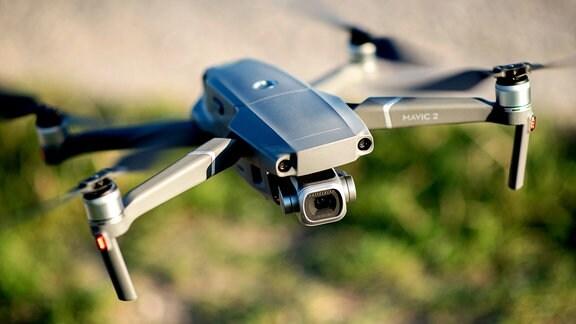 Eine moderne Kameradrohne vom Typ DJI Mavic 2 Pro fliegt über einem Feld.