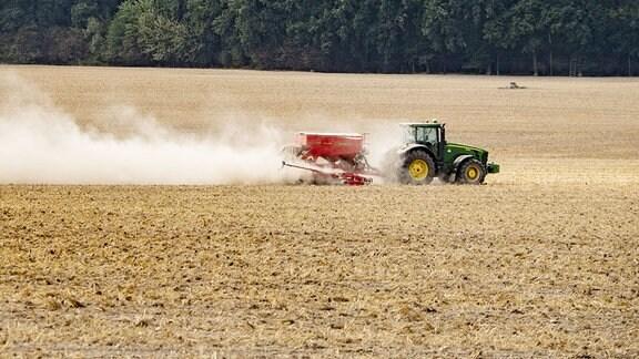 Ein Bauer düngt mit einem Traktor ein Feld bei Löbau.