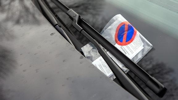 Ein Knöllchen ist an einem Fahrzeug auf einem Parkplatz an dem Scheibenwischer angebracht.