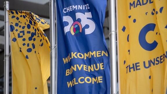 """Flaggen mit dem Logo """"Chemnitz 2025"""" wehen vor dem Neuen Rathaus."""