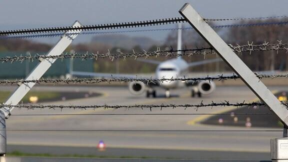 Flugzeug hinter Stacheldraht am Flughafen Frankfurt am Main