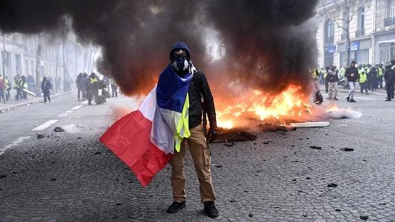 Ein maskierter Mann steht vor einer brennenden Barrikade, mit der französichen Flagge um den Körper geschlungen.