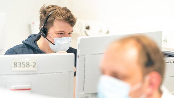 Ein Disponent sitzt in der neuen Krankenhausleitstelle Corona im Uniklinikum Dresden und koordiniert Anrufe von Patienten.