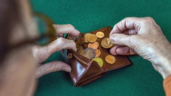 Seniorin zählt Kleingeld im Portemonnaie.