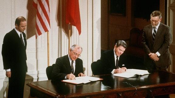US-Präsident Ronald Reagan (r) und der sowjetische Parteichef Michail Gorbatschow unterzeichnen am 08.12.87 in Washington den INF-Vertrag zur Vernichtung der atomaren Mittelstreckenraketen.