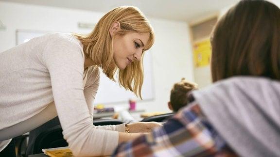Lehrerin hilft Schüler.