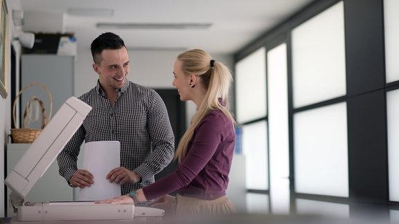 Eine Frau und ein Mann stehen in einem Büro an einem Kopiergerät und schauen sich lächelnd an.