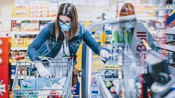Eine Frau trägt eine Schutzmaske und Handschuhe bei ihrem Einkauf in einem Supermarkt.