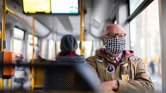 Ein Mann sitzt auf dem Weg zur Arbeit in einer Straßenbahn und trägt einen Mundschutz.
