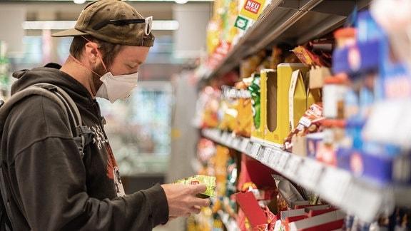 Ein Kunde steht in einem Supermarkt vor einem Regal, und trägt dabei einen Mundschutz.