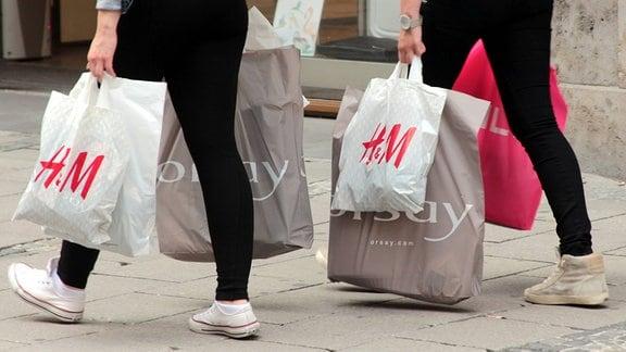 junge Frauen tragen Einkaufstaschen und Plastiktüten