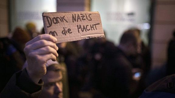 Demonstrant mit Pappschild mit Aufschrift ''Dank Nazis an die Macht''.