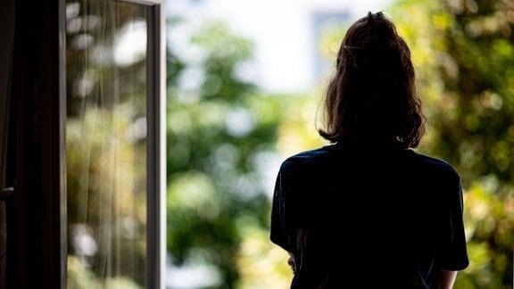 Eine Frau steht in ihrer Wohnung an einem Fenster.