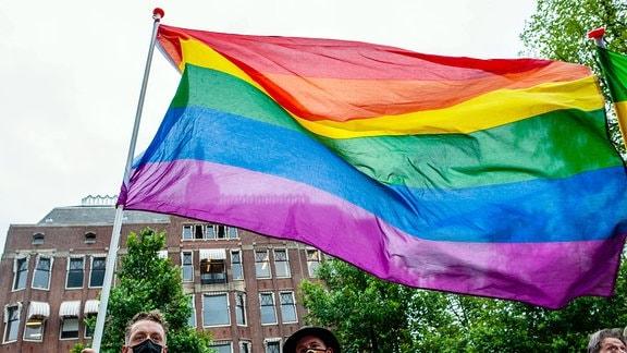 Ein Mann hält eine große Regenbogenfahne.
