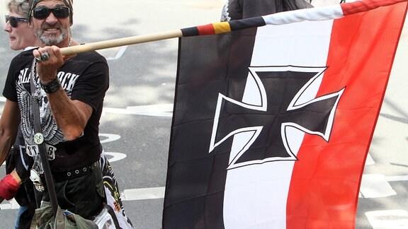 Ein Mann trägt eine schwarz weiß rote Reichskriegsflagge des Deutschen Reiches.
