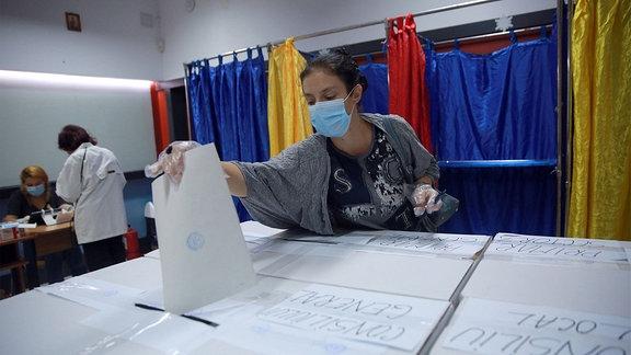 Eine junge Frau mit einer Gesichtsmaske gibt ihre Stimme bei den Kommunalwahlen in Bukarest ab
