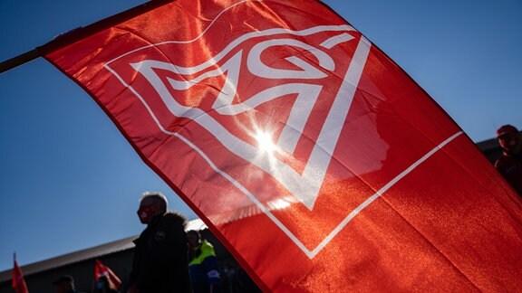Ein Streikender hält während eines Warnstreiks eine Fahne der IG-Metall Schweinfurt.