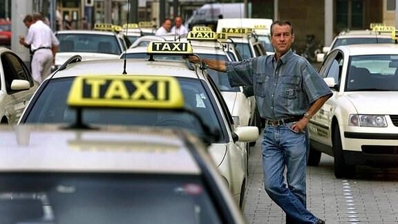 Ein Taxi-Fahrer wartet auf Kundschaft.